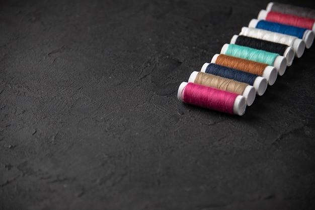 暗い床のカラフルな糸の正面図は戦争死葬儀の邪悪な縫製を縫う