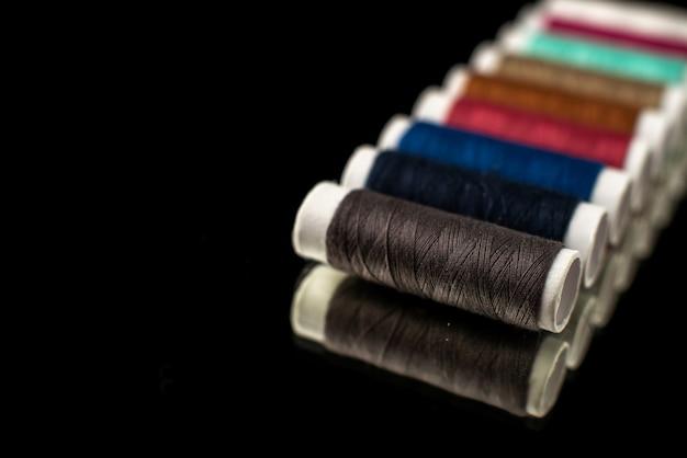 暗い表面のカラフルな糸の正面図