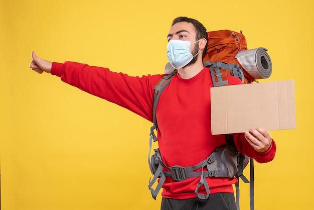 黄色い背景に書かずにシートを表示するバックパック付きの医療マスクを着た集中した旅行者の男性の正面図
