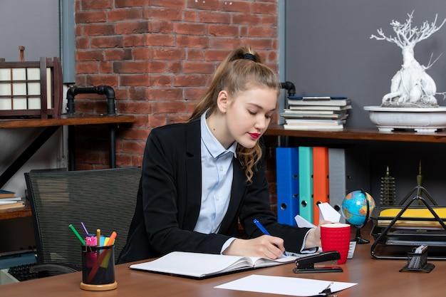 책상에 앉아 사무실에서 문서에 글을 쓰는 집중된 젊은 여성의 전면