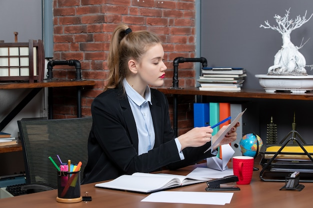 책상에 앉아 사무실에서 문서를 읽는 집중된 젊은 여성의 전면 보기