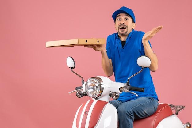 パステル調の桃の背景に注文を保持しているスクーターに座っている帽子をかぶった、心配している宅配便の男性の正面図
