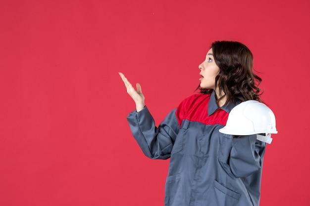 Вид спереди обеспокоенной женщины-архитектора, держащей каску и указывающей вверх справа на изолированной красной стене