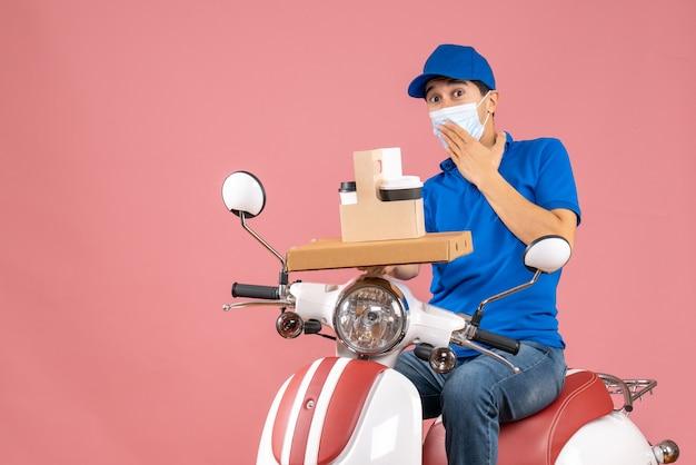 Вид спереди заинтересованного мужчины-доставщика в маске в шляпе, сидящего на скутере, доставляющего заказы на пастельном персиковом фоне
