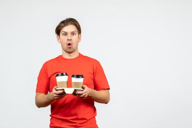 白い背景の上の紙コップでコーヒーを保持している赤いブラウスで心配している若い男の正面図