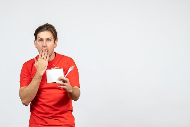 白い背景の上の紙箱とスプーンを保持している赤いブラウスで心配している若い男の正面図