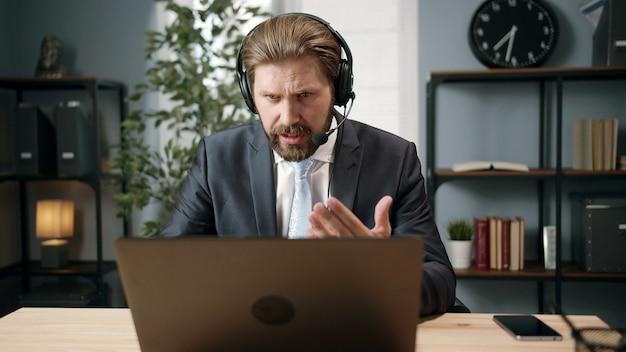 Вид спереди уверенного бизнесмена с гарнитурой, смотрящего на экран ноутбука, говорящего через интернет