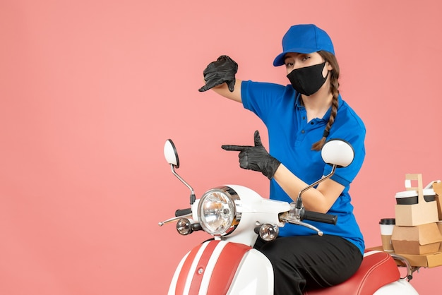 パステルピーチの背景に注文を配達するスクーターに座って医療用マスクと手袋を着た、自信を持って宅配便の女の子の正面図