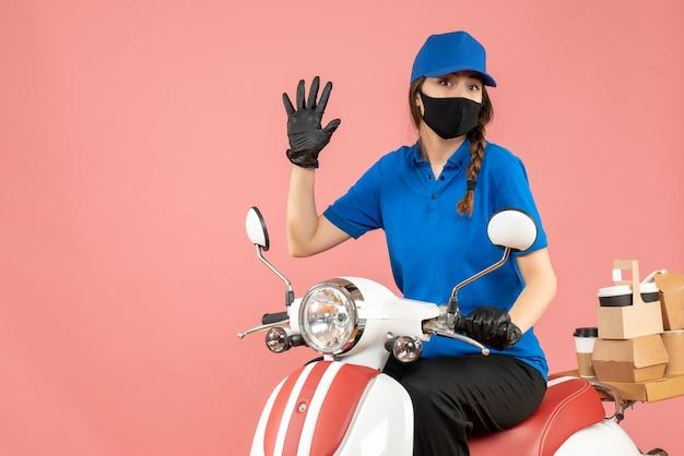 パステル調の桃の背景に5つを示す注文を配達するスクーターに座って医療用マスクと手袋をはめた、自信に満ちた宅配便の女の子の正面図