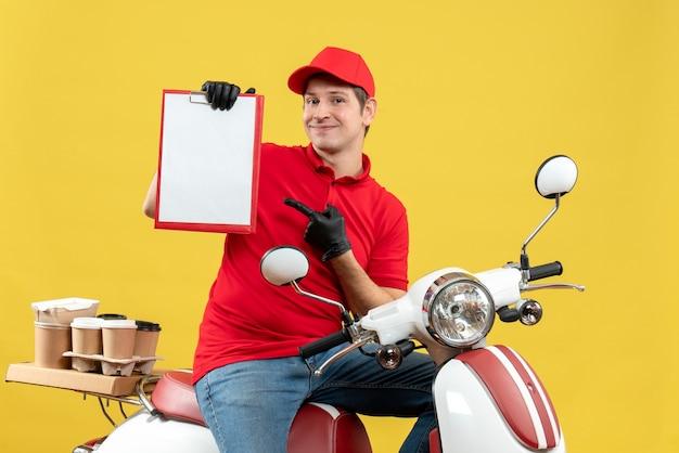 문서를 들고 스쿠터에 앉아 주문을 제공하는 의료 마스크에 빨간 블라우스와 모자 장갑을 끼고 자신감 택배 남자의 전면보기