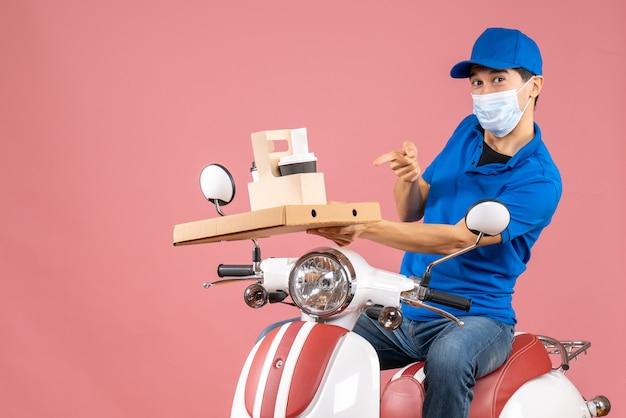 Вид спереди уверенного мужчины-доставщика в маске в шляпе, сидящего на скутере, доставляющего заказы на пастельном персиковом фоне