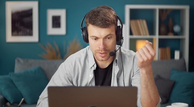 インターネットを介して話しているコンピューター画面を見ているヘッドセットと自信を持って男の正面図