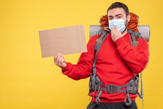 노란색 배경에 쓰지 않고 시트를 가리키는 배낭과 의료 마스크를 쓰고 자신감 여행자 남자의 전면보기