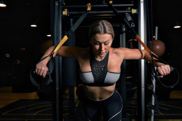 Вид спереди уверенно молодая блондинка делает тренировки по поднятию тяжестей привлекательная молодая женщина, поднятие тяжестей, с нетерпением жду сильный тренированные формы тела руки грудь ноги.