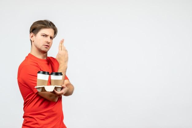 紙コップでコーヒーを保持し、白い背景で銃のジェスチャーを作る赤いブラウスで自信を持って若い男の正面図