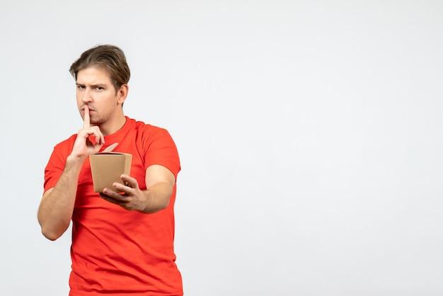 小さな箱を保持し、白い背景で沈黙のジェスチャーをしている赤いブラウスで自信を持って若い男の正面図
