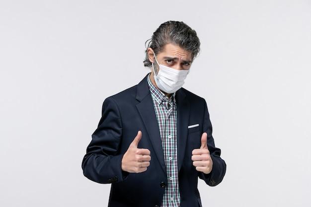 マスクを着用し、白い表面で大丈夫ジェスチャーをしているスーツの自信を持って若い男の正面図