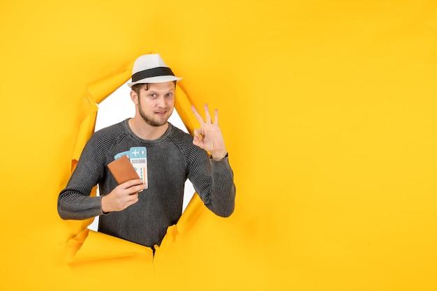 チケットを持った外国のパスポートを持ち、黄色い壁に破れた眼鏡のジェスチャーをする帽子をかぶった自信に満ちた若い男性の正面図