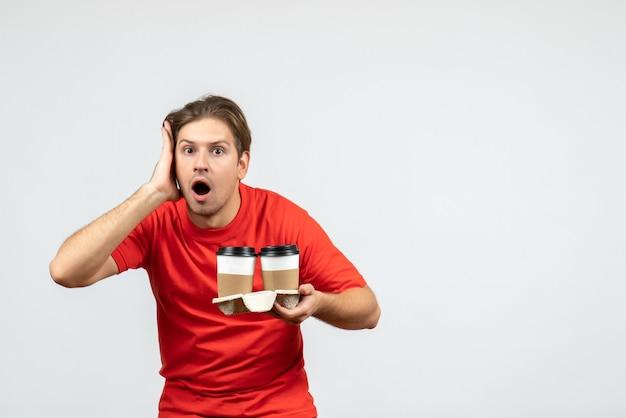 白い背景の上の紙コップでコーヒーを保持している赤いブラウスの混乱と感情的な若い男の正面図