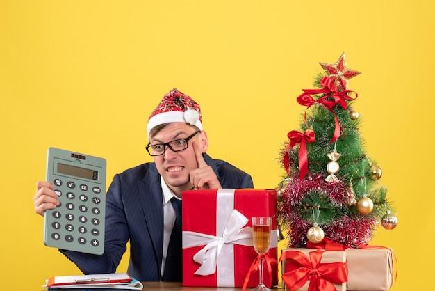 Вид спереди сбитого с толку делового человека с калькулятором, сидящего за столом возле рождественской елки и подарков на желтом