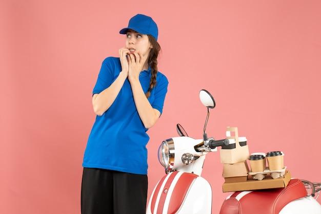 Вид спереди сбитой с толку дамы-курьера, стоящей рядом с мотоциклом с кофе и небольшими пирожными на нем на фоне пастельного персикового цвета