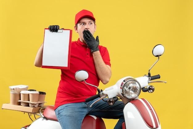 문서를 들고 스쿠터에 앉아 주문을 제공하는 의료 마스크에 빨간 블라우스와 모자 장갑을 끼고 혼란 택배 남자의 전면보기