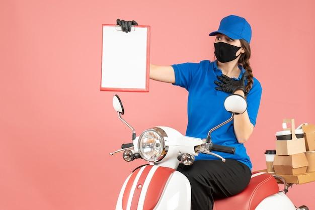 医療マスクと手袋を着て、パステルピーチの背景に注文を配達する空の紙のシートを持ったスクーターに座っている混乱した宅配便の女性の正面図