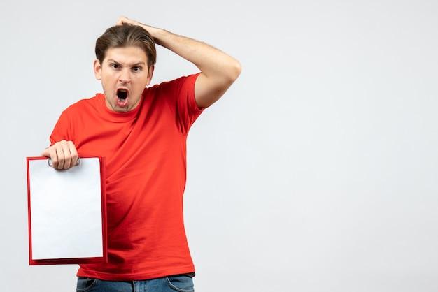 白い背景の上のドキュメントを保持している赤いブラウスの混乱した感情的な若い男の正面図