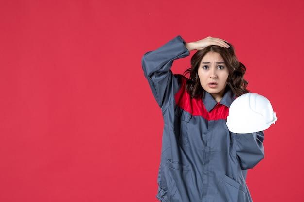 ハード帽子を保持し、孤立した赤い壁に彼女の頭に手を置く混乱した女性建築家の正面図
