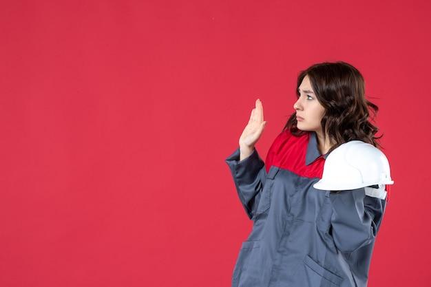 하드 모자를 들고 고립 된 붉은 벽에 서 혼란 스 러 워 여성 건축가의 전면보기