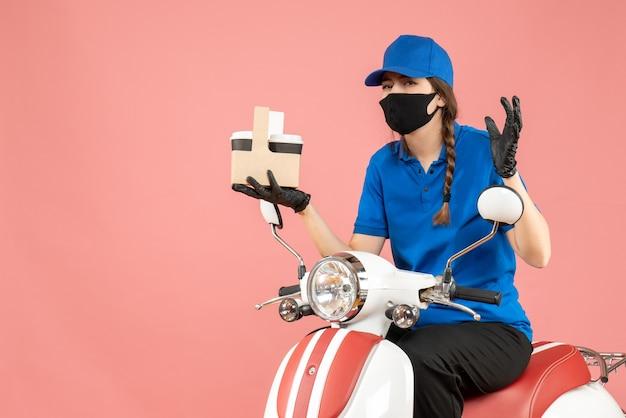 医療用マスクと手袋を着て、パステル調の桃の背景に注文を配達するスクーターに座っている混乱した女性の配達員の正面図