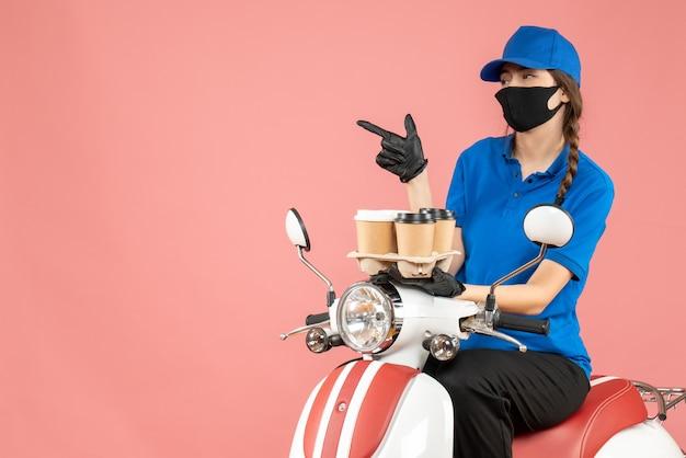 パステル調の桃の背景に注文を保持しているスクーターに座って医療用マスクと手袋をはめた混乱した女性配達員の正面図