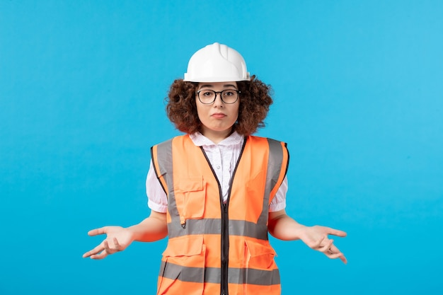 파란색 벽에 유니폼에 혼란 스 러 워 여성 노동자의 전면보기