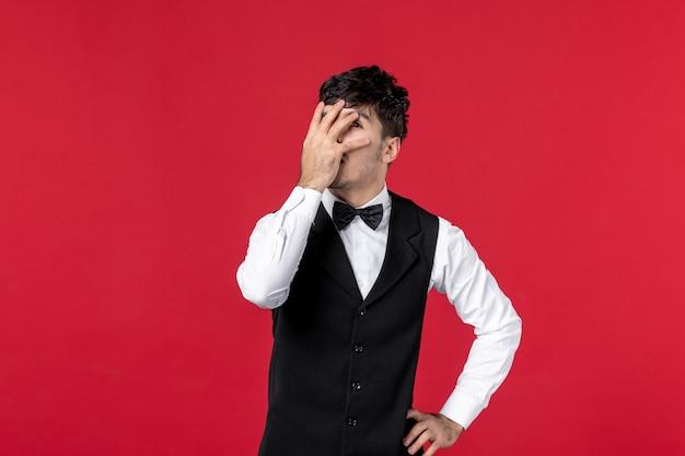 赤い壁に顔に手を置く首に蝶と制服を着た混乱した男性ウェイターの正面