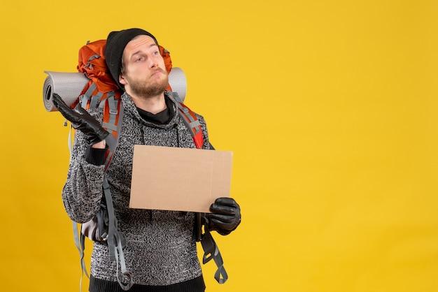 Вид спереди сбитого с толку человека-туриста с кожаными перчатками и рюкзаком, держащим чистый картон