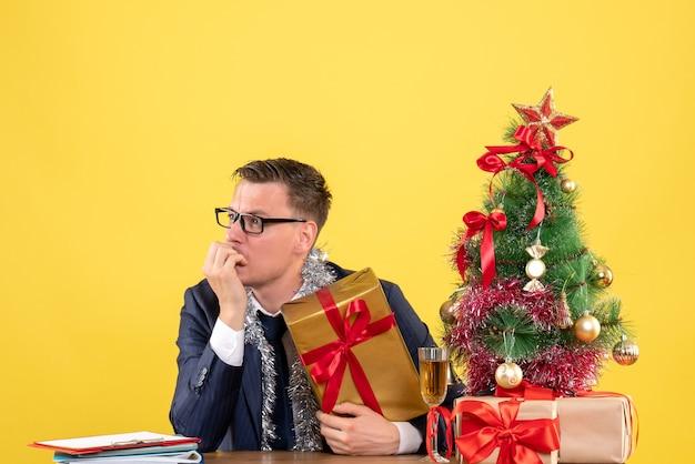クリスマスツリーの近くのテーブルに座って、黄色で提示する左を見ている混乱した男の正面図