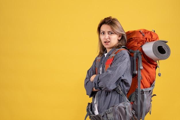 赤いバックパックの交差点の手と混乱した旅行者の女性の正面図