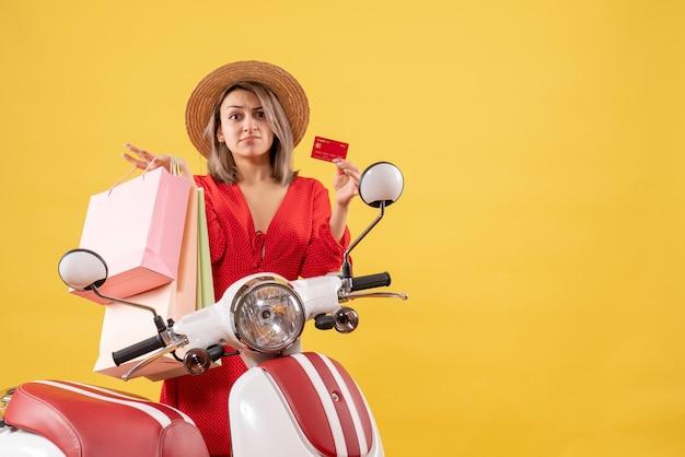 쇼핑 가방과 카드를 들고 오토바이에 빨간 드레스에 혼란 스 러 워 여자의 전면보기