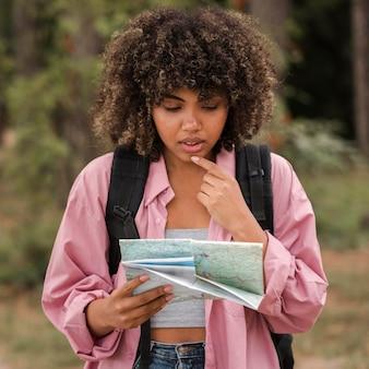 屋外でキャンプしながら地図を見ている混乱した女性の正面図
