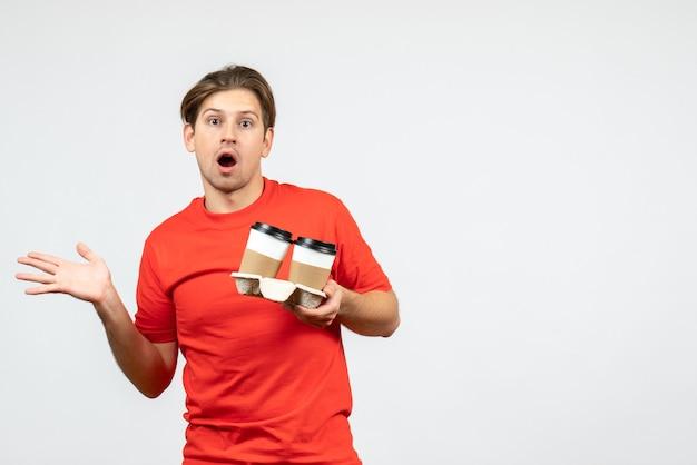 紙コップでコーヒーを保持し、白い背景の右側に何かを指している赤いブラウスで混乱している若い男の正面図