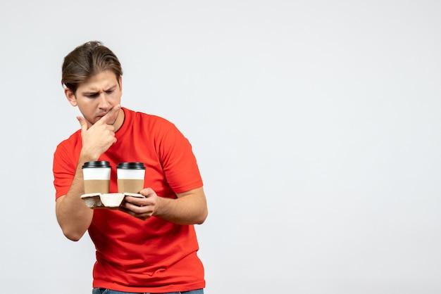 白い背景の上の紙コップでコーヒーを保持している赤いブラウスで混乱している若い男の正面図