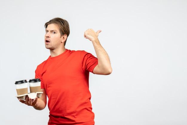 白い背景に戻って指している紙コップでコーヒーを保持している赤いブラウスで混乱している若い男の正面図