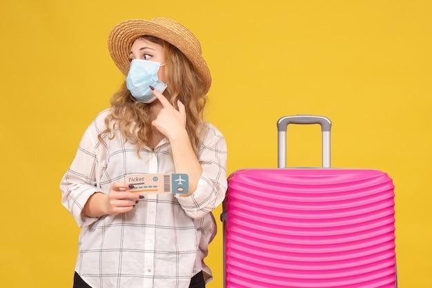 チケットを表示し、ピンクのバッグの近くに立っているマスクを身に着けている混乱した若い女性の正面図
