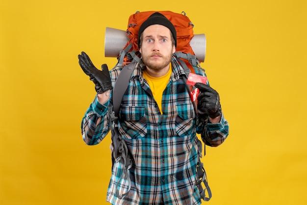 Вид спереди сбитого с толку молодого путешественника с рюкзаком, держащим кредитную карту