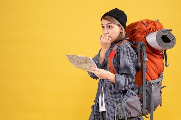 黄色の壁に立っている地図を保持しているバックパックと混乱した若い旅行者の正面図