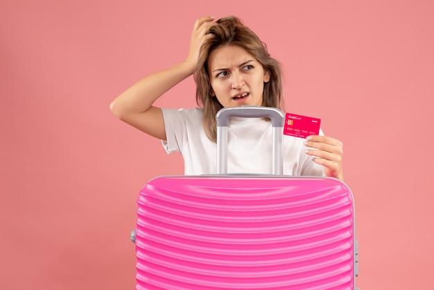 ピンクのスーツケースの後ろにカードを保持している混乱した若い女性の正面図
