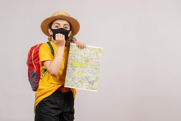 灰色の壁に地図を保持しているバックパックと混乱した若い女性の正面図