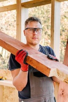 安全メガネと木片を持った建設作業員の正面図