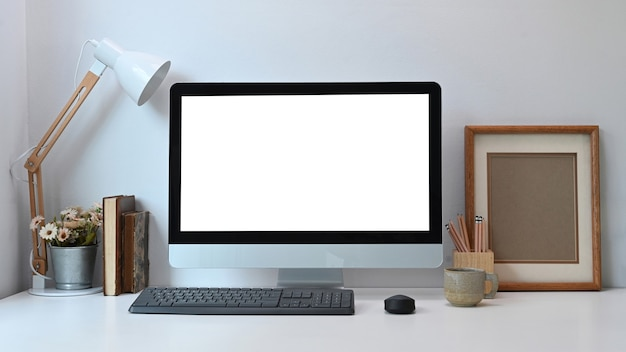 Вид спереди современного рабочего места с белым компьютером монитора пустого экрана и оборудованием на белом столе.
