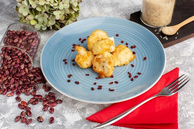 흰 빛 책상에 쌀과 콩이 든 파란색 접시 안에 조리 된 콜리 플라워의 전면보기